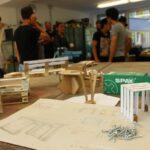 Das Foto zeigt einen Bauplan und Modelle aus Pappe