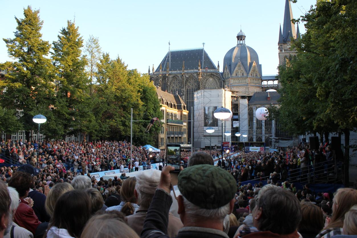 Das Foto zeigt eine Menschenmenge und eine Person beim Hochsprung