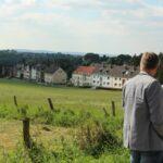 Das Foto zeigt eine ländliche Gegend und zwei Herren die sich unterhalten