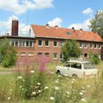 Das Foto zeigt ein Haus mit Garten und einem Auto