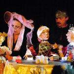 Das Foto zeigt zwei Menschen die an einem Tisch mit Puppen bei einem Kaffekränzchen sitzen