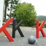 Das Foto zeigt drei K-Skulpturen auf einem Hof