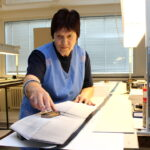 Das Foto zeigt eine Frau bei der Arbeit an einem Papierstapel