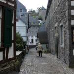 Das Foto zeigt eine Altstadt und zwei Menschen die Arm in Arm die Straße entlang gehen
