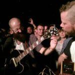 Das Foto zeigt einen Mann mit Gitarre in einer Menschenmenge