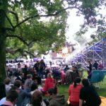 Das Foto zeigt eine Menschenmenge auf einer Wiese vor einer Bühne
