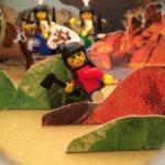 Das Foto zeigt Playmobil Indianer in einer Landschaft aus Papierhügeln