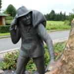 Das Foto zeigt ein Denkmal. Die Statue, ein Mann, trägt einen Sack auf dem Rücken