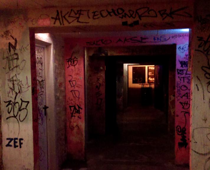 Das Foto zeigt das Innere eines dunklen Gebäudes mit Grafitti an den Wänden