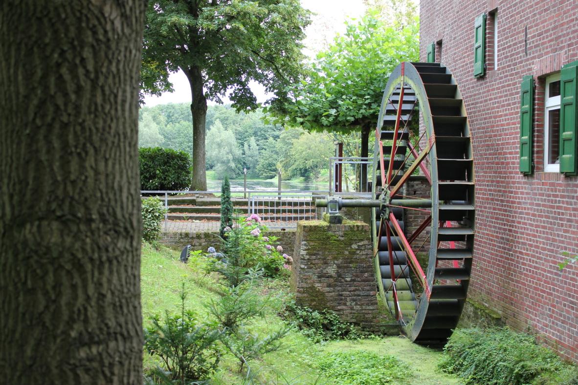 Das Foto zeigt ein Haus mit einem Wasserrad